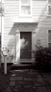 Exterior of Chester Moffett House door featuring shingle siding, and window mouldings.