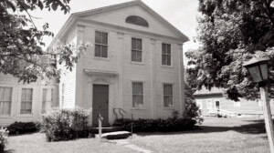 Exterior of Lew Lawyer House with cornice mouldings, and door casing with panel molds, and column detail.