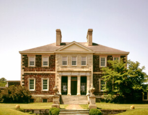 Palladian style house features nearly perfect symmetry, brick walls, window mouldings, cornice mouldings, and a covered entrance with columns.