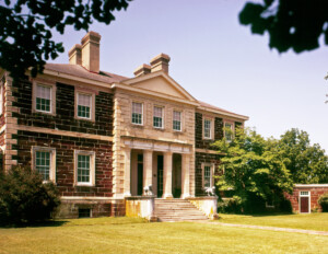 A side angle of a palladian style house featuring perfect symmetry, brick walls, window mouldings, cornice mouldings, and a covered entrance.