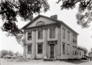 Exterior of Peter Allen House featuring four columns, covered front porch, front door with column detail, and panel molds.