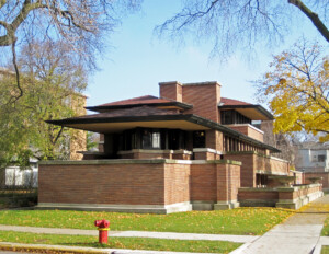 Prairie style house with low-pitched hipped roof, bank of window mouldings, horizontal banding, wide roof eaves, and an all brick exterior.