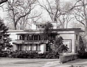 Prairie style house with flat roof, bank of window mouldings, and stucco exterior.