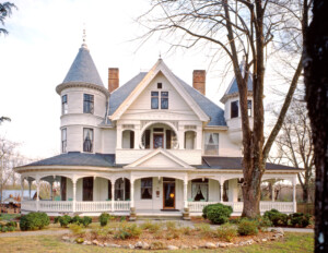 Victorian style castle with window mouldings and shutters, cornice mouldings, overhanging roof, and covered porch.
