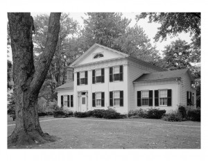 Side angle of exterior of John Mathews House with windows with shutters, and large columns in front.