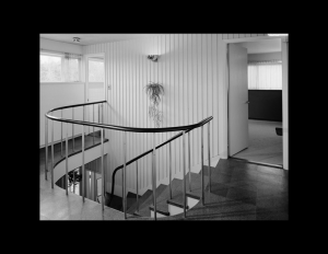 Interior of an international style house that has wrap around stair railings, door mouldings and window mouldings.
