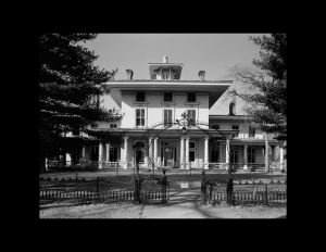 Italianate style house with gable on roof, tall windows, and covered front porch with columns.