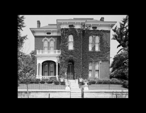 Italianate style home with hipped roof, tall window mouldings, covered walkway to entrance along with a balcony on top with balustrades.