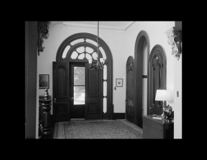 Interior of italianate style room with oval door mouldings, and cornice mouldings.