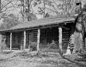 Log Cabin Style home with traditional logs, outside brick chimney, and hangover roof creating a covered porch being upheld with log columns.