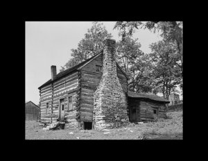 Small log cabin style home with outside brick chimney, stairs leading to entrance way, and a steep roof.
