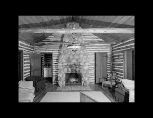 Interior of log cabin style house with round stone chimney, handcrafted log walls, hardwood floors, and log beam going across ceiling.