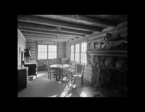 Interior of log cabin style home with many log beams going across ceiling, traditional log walls, window mouldings, and carpeted floor.