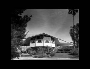 Mid century style house with flat roof that is slanted, and hexagon sunroom with window mouldings.