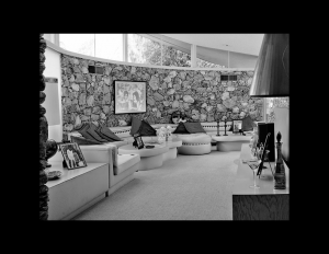 Interior of mid century style room that features rock walls, and window mouldings outlining the room close to the ceiling.