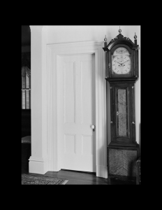 Interior of octagonal plan style room with door mouldings, and standing clock.