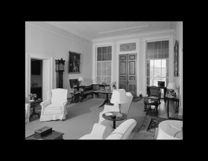 Interior of palladian style house has door mouldings, window mouldings, ceiling mouldings, hardwood floors, and is whitewashed.