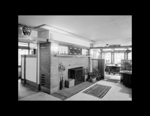 Interior of prairie style house with brick fireplace, and window mouldings.