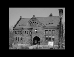 Romanesque style building featuring all stone walls, window mouldings, conical side tower, and covered entrance way with steps.