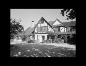 Tudor style house with hipped roof, window mouldings, and door mouldings.
