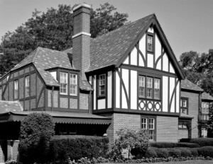 Tudor style house with hipped roof, window mouldings, and brick chimney.
