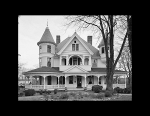 Exterior house with victorian style featuring a wrap-around porch, window mouldings, balcony on second floor, and conical towers on both sides.