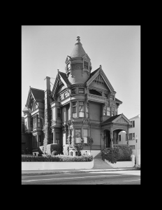 Exterior of building with Victorian style featuring a conical tower, window mouldings, and cornice mouldings.