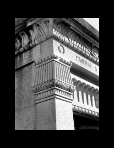 Close up of exterior egyptian revival style building featuring an egyptain revival style exterior stone cornice and stone column.