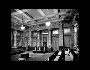 Interior of an egyptian revival style building showcasing two columns, interior cornice, wall mouldings, and door mouldings.