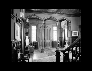 Interior of gothic revival style entrance room column mouldings, ceiling panel mouldings, door mouldings, and staircase baluster.