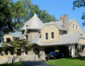 Shingle style house featuring a high pitched hipped roof, all stone banded chimney, covered entrance walkway, and window mouldings.