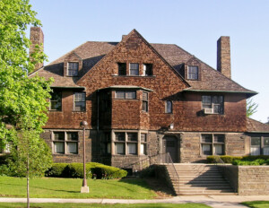 Shingle style house has the upper half with shingles, and lower half with stone, and also has window and door mouldings.