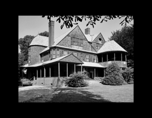 Shingle style building with balcony on first and second floor, high pitched hipped roof, and many window mouldings.