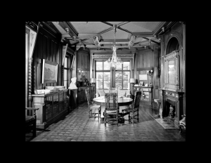 Interior of a stick style room featuring ceiling mouldings, cornice mouldings, window mouldings, and dining room table.