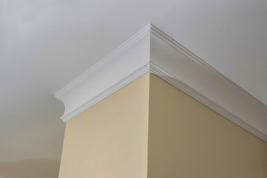 White PVC crown moulding outlines the top of a cream colored wall